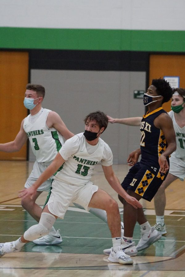 Junior Zack Sheridan (left) and senior Sam Sommerfeld (middle) in a game against Pius XI high school.
